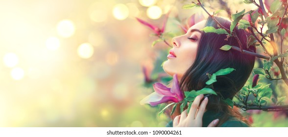 Beauty young woman enjoying nature in spring magnolia garden, Happy Beautiful brunette girl in Garden with blooming pink magnolia trees. Romantic fashion model in blossom flowers portrait