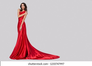 Beauty young woman in fluttering red dress. Gray background.