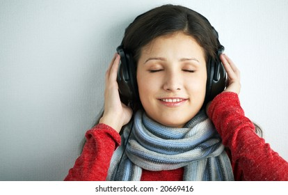 beauty young woman with headphones on gray background