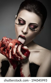 Beauty young woman licks blood from human heart against grey background