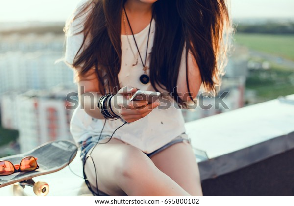 Beauty Young woman listening music on the roof, outdoor fashion portrait, smartphone play list, close up, sunglasses