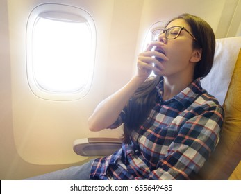beauty young woman passenger taking the airliner at morning feeling tired and showing yawning posing want to sleep on airplane.