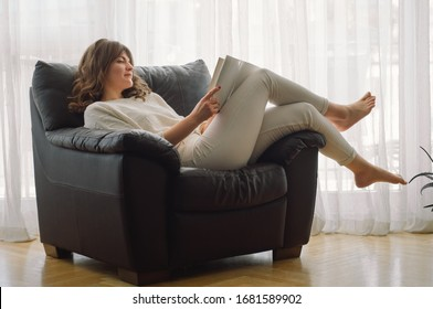 Beauty young woman is reading a book at home. Thoughtful girl reading important book. Reading and development