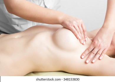 Beauty young woman recieving breast massage at spa. masseur's hands on the woman's breast