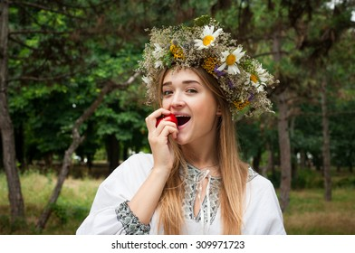 beauty young woman wearing tradisional closes and wreath holding tomato
