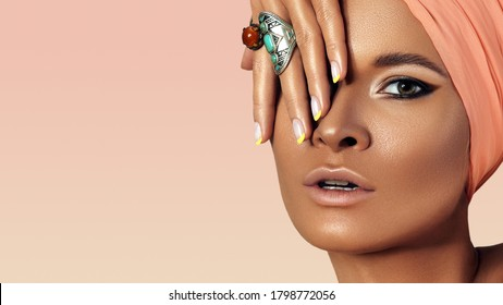 Beauty young Woman wearing Turban. Oriental Boho Style with Bohemian Accessories, Beautiful Rings, Fashion Make-up. Tanned Smooth Skin, Dark Arabian Makeup, Luxury Jewelry Rings and Perfect Manicure