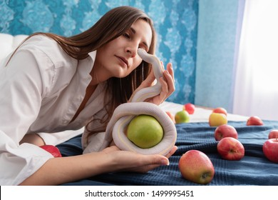 beauty young woman with white american queen snake and green apple lying on the bed. Around scattered apples. The image of biblical eve in the modern world.