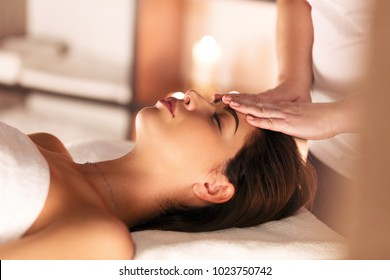 Beauty and youth. Hands of the masseuse make massage for a beautiful charming woman lying in a spa salon on a massage table.Traditional oriental massage therapy and beauty treatments.