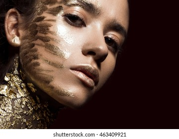 Beautyful girl with gold glitter on her face. Art image beauty