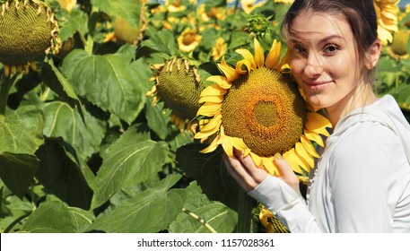 Beautyful joyful girl with sunflower enjoying nature on sunflower field. Copyspace for your design, text