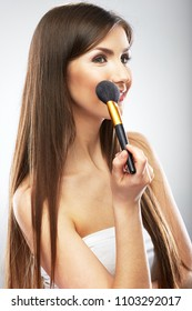 Beautyful woman applying  make up with brush. Smiling girl isolated beauty portrait.