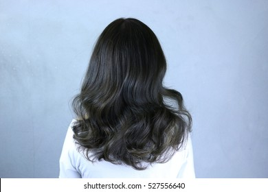 Beautyful women's hair with Brown ash color,gold highlight and curly hairstyle.back side view on white background.