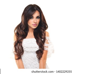 Beautyful young woman with long wavy brown hair. Attractive face and makeup. Cute dress. Isolated  white background
