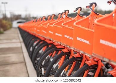 Beaverton, OR / USA - December 24 2018: Rows of orange ride sharing Biketown Nike bikes parked by the curb.