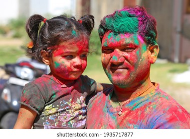 Beawar, Rajasthan, India, March 24, 2016: Portrait of Indian man with daughter smeared in color powder celebrate Holi, the Hindu spring festival of colors, in Beawar. Photo: Sumit Saraswat