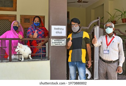 Beawar, Rajasthan, India, May 15, 2021: Satyanarayan Sharma (R) along with family applied 'Vaccinated Family' poster outside his house, first-of-its-kind initiative to encourages people in Beawar.