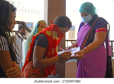 Beawar, Rajasthan, India - May 7, 2020: An anganwadi worker wearing protective face mask distribute wheat to poor women amid ongoing nationwide COVID-19 lockdown.