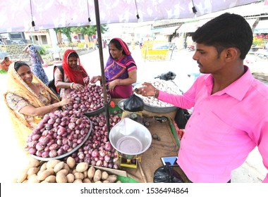 Beawar, Rajasthan, India, September 30, 2019 : Indian women buys red onions from a vegetable vendor in indian market. Photo/Sumit Saraswat