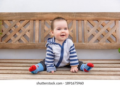 Bebe pequeño chica jugando sentada en suelo con cesped en jardin de casa con sudadera con capucha