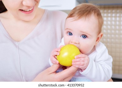 Bebe eats yellow apple. Mom is smiling and happy