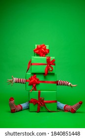 Because pyramid of green Christmas gift boxes on green background in Studio, you can see arms and legs stretched out in different directions. lot gifts for Christmas. Advertising and discounts.