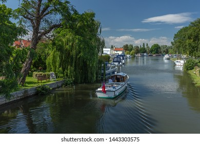 BECCLES, UNITED KINGDOM - JULY 5, 2019: A small motorboat cruises towards the Quay on the River Waveney in the picturesque market town of Beccles.