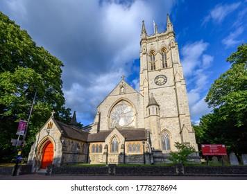 Beckenham (Greater London), Kent / UK - Jul 16 2020: St George's Church in Beckenham with square church tower, circular stained glass window and sign. A Church of England parish church in Beckenham.