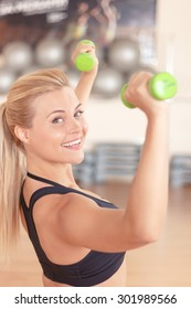 To become fit. Portrait of young pretty smiling blond-haired woman doing fitness exercises by using little dumbbells.