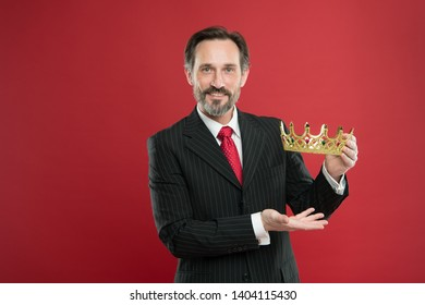 Become king ceremony. Award and achievement. Feeling superiority. Being superior human. Monarchy attribute. Monarchy family traditions. Man bearded guy in suit hold golden crown symbol of monarchy.