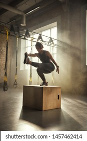 Becoming the best. Side view of athletic woman in sportswear doing squat and training legs while standing on wooden box at gym.