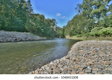 Becva River has left the city and flows further with one bank bluish, lined with trees and bushes.