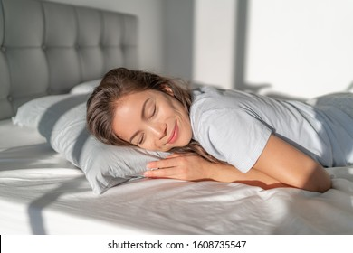 Bed Asian girl happy smiling sleeping on stomach sleeper resting head on foam pillow. Healthy sleep.