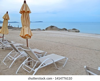 Bed beach and yellow umbrella on tropical beach in the summer morning. Nature and travel concept.