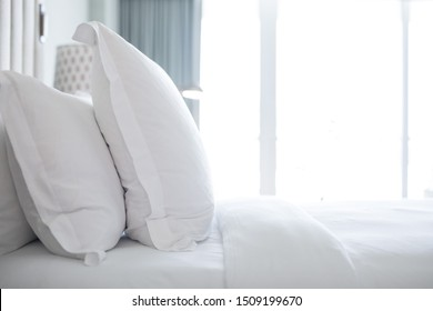 Bed in a bedroom hotel room with white sheets, large pillows cushions against a bright white background window lit by natural light simple clean modern simple elegant