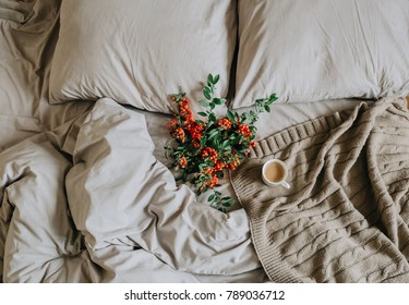 bed with bedspread, grey sheet and pillowsand cup of coffee