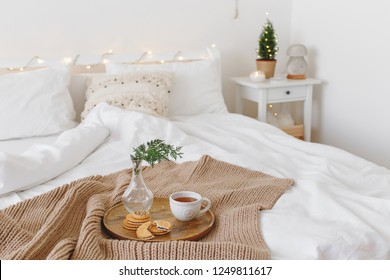Bed with beige knitted blanket, cup of tea, cookies and vase with coniferous twig on wooden tray. Christmas or new year winter home interior decor. Holiday decorated room. White stylish cozy bedroom.
