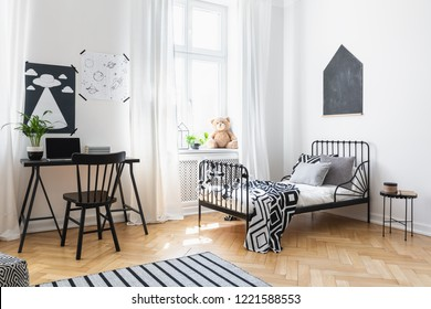 Bed and black chair at desk in kid's room interior with posters and plush toy on window sill. Real photo