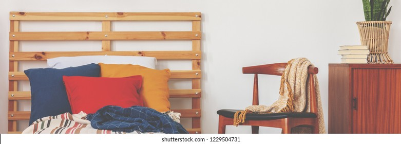 Bed with blue, carmine and ochre pillows placed in white bedroom interior with blanket on chair and retro cupboard with books and plant in real photo