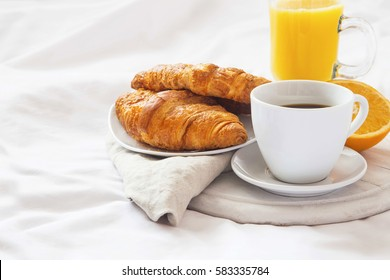 Bed breakfast with coffee cup, croissants and orange juice on white sheets