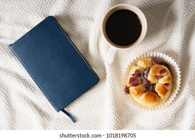 bed breakfast with coffee cup and sweet bread on white blanket