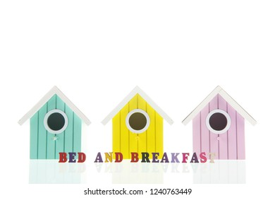 Bed and breakfast in little colorful birdhouses isolated over white background