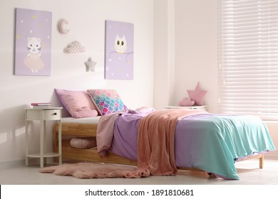 Bed with colorful linen in stylish children's room. Interior design