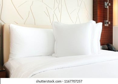 bed covered with white sheets and pillows. The wall is made by wooden wallpaper, tables are put aside with clock and telephone