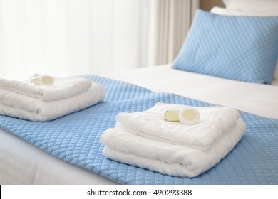 Bed with fresh towels and amenities