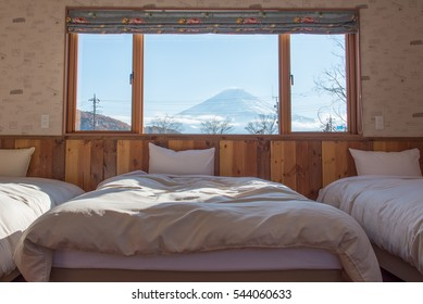 Bed with Fuji mountain view as a background when looking outside the window.