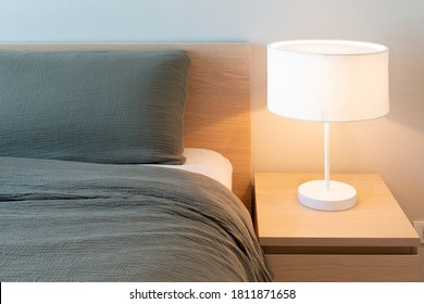 Bed with gray blanket and pillow with white electric lamp on the bedside table in bedroom interior. Minimalist comfort bedroom design for everyday living. Copy space, horizontal. Real image.