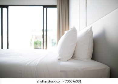 Bed in hotel room or home with white sheets lit by natural light from with window in the background and plenty of blank copy space