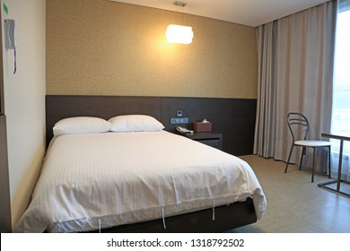 Bed in hotel room with window for travelers