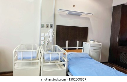 a bed and infants crib covered by blue bed sheet and oxygen tank on white wall, a room on ward for mother and babies after giving a birth/delivery in modern interior style
