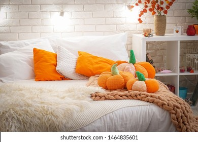 bed with light bed linen covered with a knitted blanket of coarse yarn. in the bedroom on the bed are pumpkin textiles. autumn furnished in light airy style.